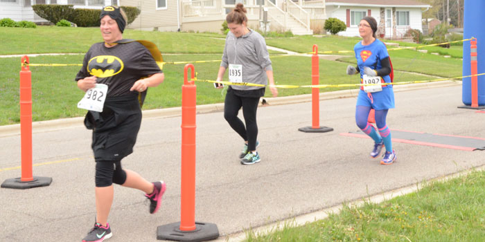 From left, Patty Richardson,  Syracuse, Kearstin Criswell, Warsaw, and Krystal Smith, Warsaw, cross the finish line. (Photos by Amanda McFarland)