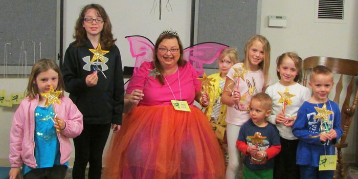 The Book Fairy, Julie Frew, reads Fairy Tales to story time children on Wednesday, April 6. The children created fairy wands during craft time. Here they pose for a picture with the Book Fairy and their finished wands. Listed from the left are Zoey Rushlow, Apryl Wray, Julia Frew, Ava Makinson, Myla Miller, Alex Miller, Shelby Miller, and Charlie Miller.