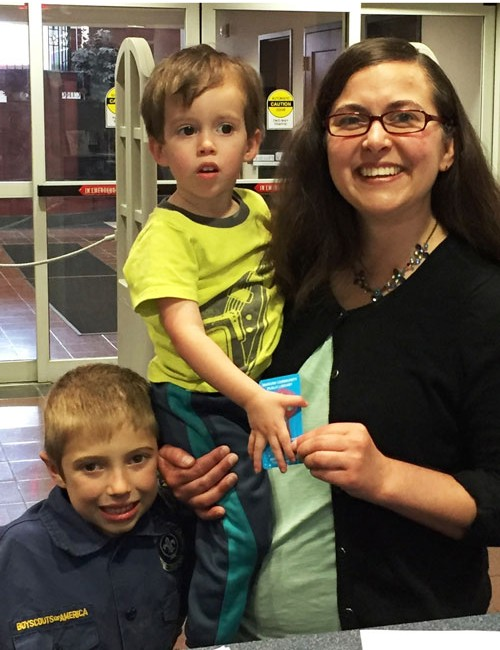 New Children's Librarian, Katie Warrener, signs up for her WCPL library card while accompanied by her nephews Kevin and Henry Gough.