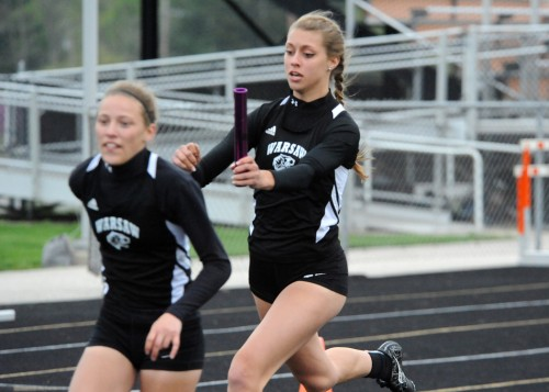 Sam Alexander exchanges with Abbi Curtis in Warsaw's winning 4x100 relay.