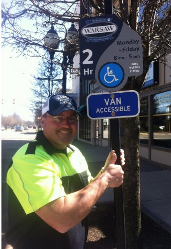 City Parking Control Officer Dana Hewitt shows off the new handicapped accessible signs installed downtown Warsaw.
