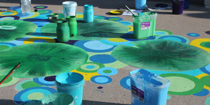 Some storm drain paintings will be interactive in nature and can be located outside of community buildings, such as this hopscotch painting in progress outside of the Kosciusko County Community Foundation. (Photo provided)