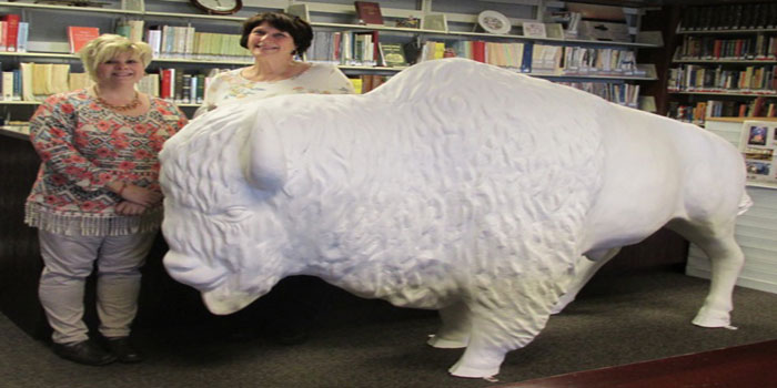 North Webster Library clerk Molly Barton and Adult Services Director Beth Smith take possession of the unfinished fiberglass bison statue when it was delivered to the library. It will soon be turned over to the Barrett Family Artists to paint and decorate before being displayed outside the library.