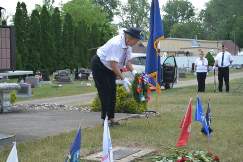 Lorraine Carson, chaplain of the Syracuse American Legion Post 223, lays a Memorial Day wreath during a ceremony at the Syracuse Cemetery.