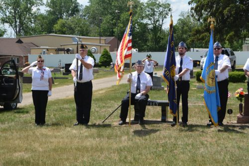 Members of the Syracuse American Legion Post 223 stand at attention during the playing of Taps by Lorree Corbat, a member of the Legion Women's Auxiliary.