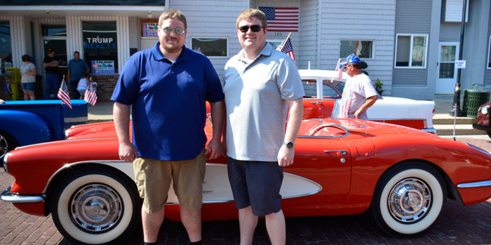 David and Dan Ferguson pose in front of the corvette they would drive in the parade.
