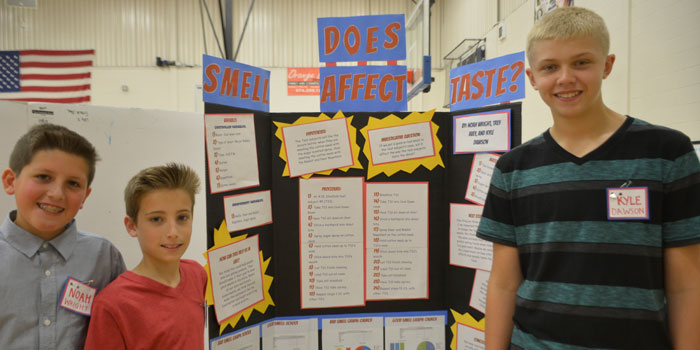 """From the left, Noah Wright, Trey Avey and Kyle Dawson pose in front of their project titled, """"How Does Smell Affect Taste?"""""""