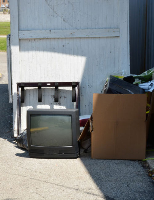 An abandoned CRT television sitting outside Our Father's House donation box.