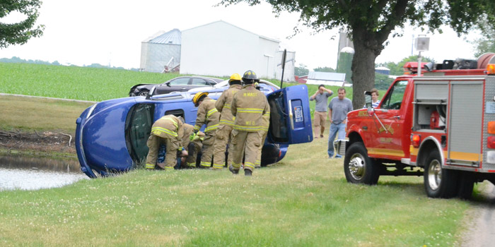 Milford Firefighters use the sun roof on the Chevrolet mini van to extricate the driver.
