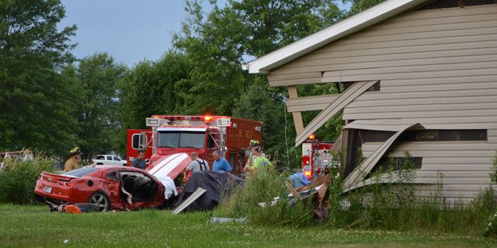 Crews work to free the passenger and driver of a vehicle that collided with a house. (Photos by Amanda McFarland)