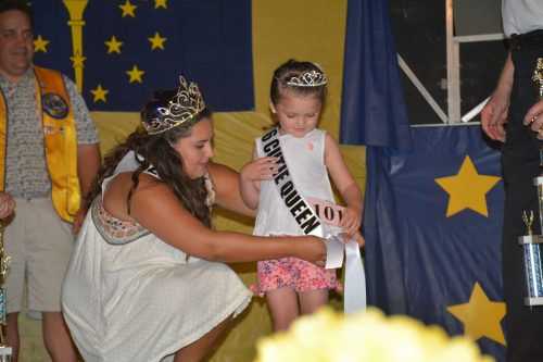 2016 Mermaid Festival Cutie Queen Addyson Thomas receives her sash from 2015 Queen of the Lakes Kensea Myers.
