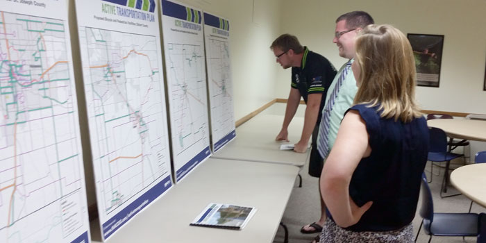From left, Greg Demopoulos, MACOG Principal Planner Zachery Dripps and MACOG Regional Planner Caitlin Stevens review maps outlining proposed walk and bike routes. (Photo by Amanda McFarland)