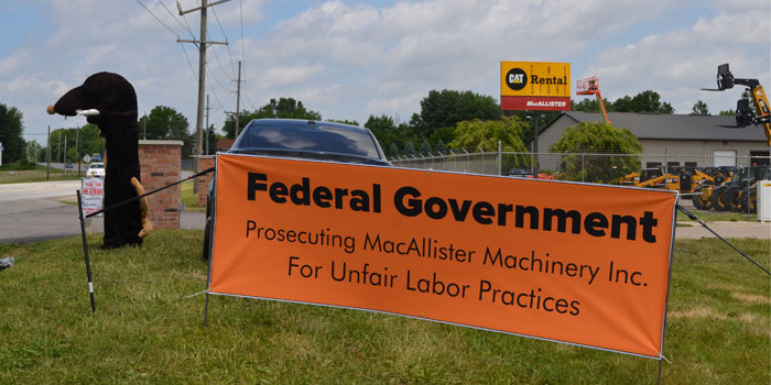 Representatives of the Local 150 sit next to a sign outside MacAllister Equipment, Warsaw. (Photo by Amanda McFarland)
