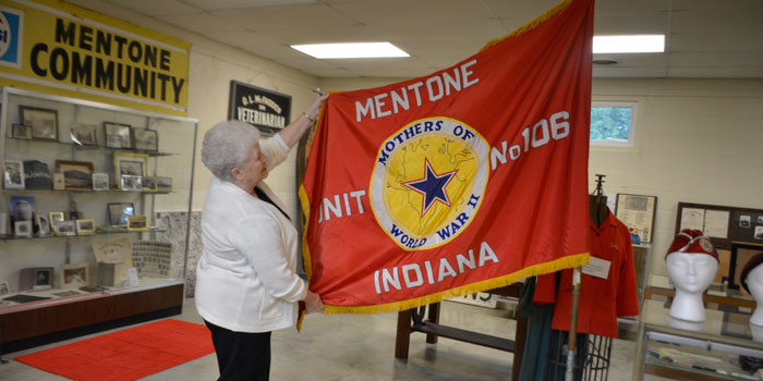 Linda Cochran holding up the flag of the Mentone chapter of Mothers Of World War 2.