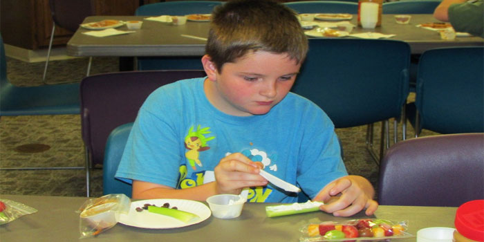 Andrew Bradley makes his snack Ant on a Log with Raisins, Celery, and Cream Cheese at our First Food and Fun Session on June 15 where kids learned how to make healthy treats!
