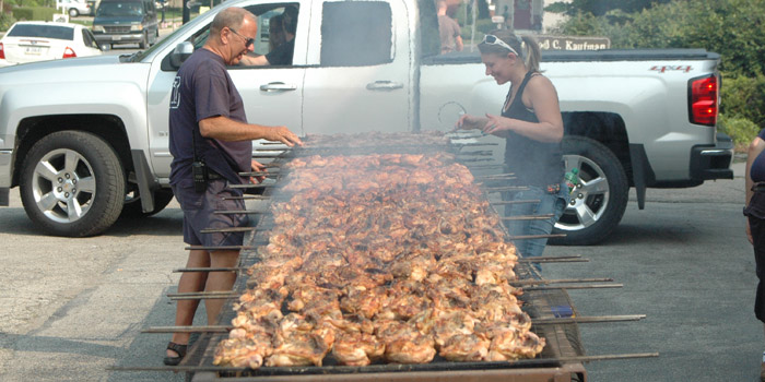 Turkey Creek Fire Department members Joe Anderson and Tameka Lucas tend the grill for last year's barbecue fundraiser. The department will commence serving the chicken, pork and corn on the cob at 10 a.m. Saturday, July 2, outside of Fire Station 1 in Syracuse. (Photo by David Hazeldine)