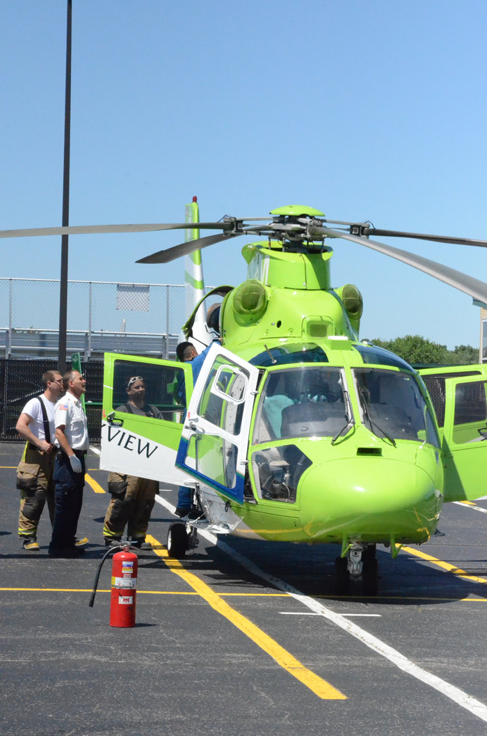Firefighters check the helicopter engine with the pilot.