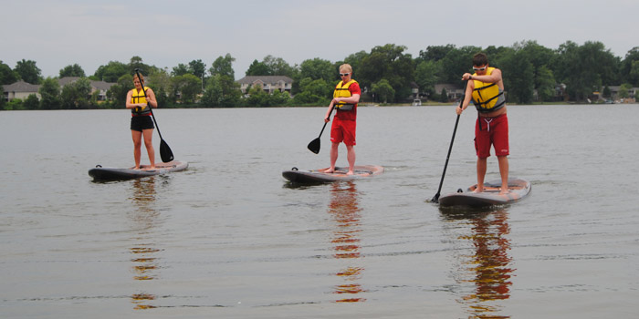 Free paddle boarding is offered at Pike Lake in Warsaw through Saturday, Aug. 20. Pictured paddle boarding, from left, are Ramie Perry, Ethan Cook and Kaleb Schneidewent. (Photos by Phoebe Muthart)