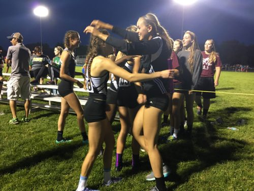 Audrey Rich is smothered by teammate Dayton Groninger after Rich brought home a regional title in the 4x400 relay.