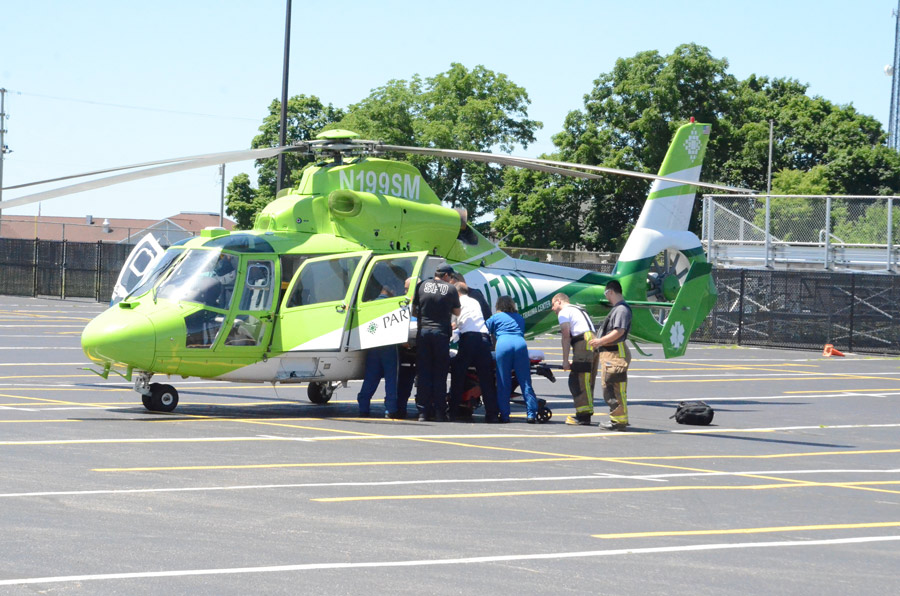 Firefighters and paramedics, along with Samaritan 2 medical crew transfer Terry Powell from the helicopter to the ambulance after a sensor indicated a potential engine issue in the helicopter. (Photo by Deb Patterson)