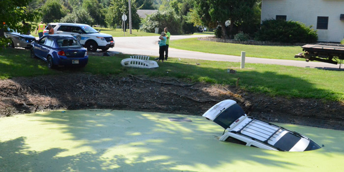 A Jeep Cherokee is partially submerged in a pond following a two-vehicle accident. (Photos by Deb Patterson)