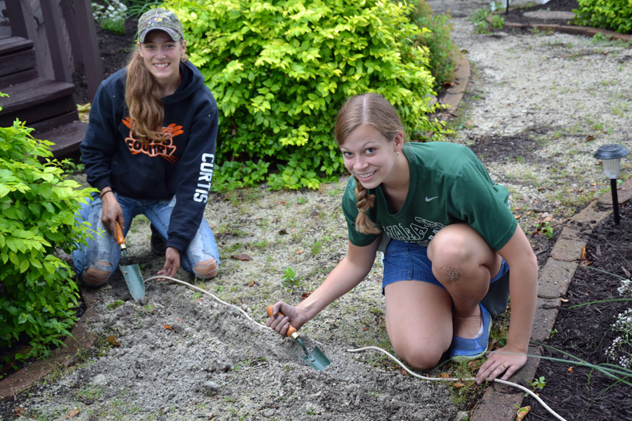 Abbi Curtis and Lacey Helfers help bury wires in the garden during one of last year's garden workdays. They both are part of Junior Leaders and dedicated their time toward maintaining the garden.