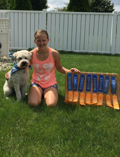 Baxter poses with his human buddy and a collection of ribbons they have won together.