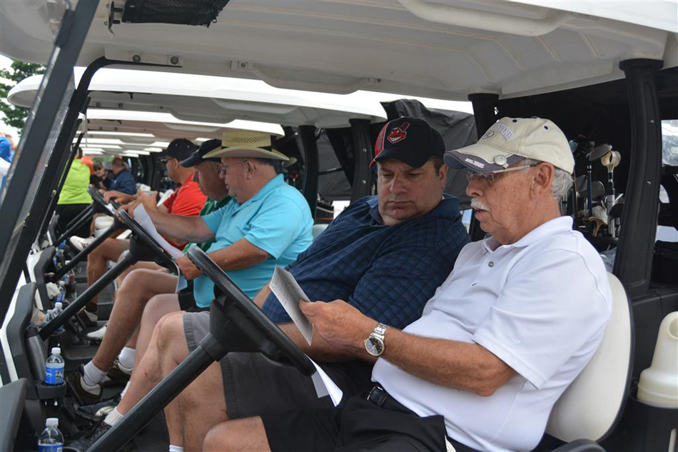 Marty Becker, near in white, reviews the golf program ahead of the ninth-annual Warsaw Optimist Golf Outing. (Photo provided)