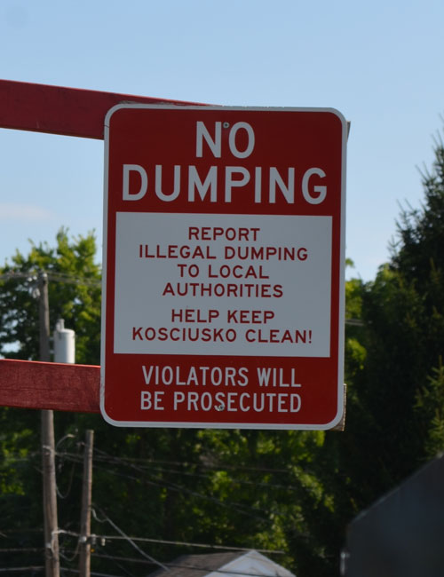 A sign near the recycling bins warns users against dumping.