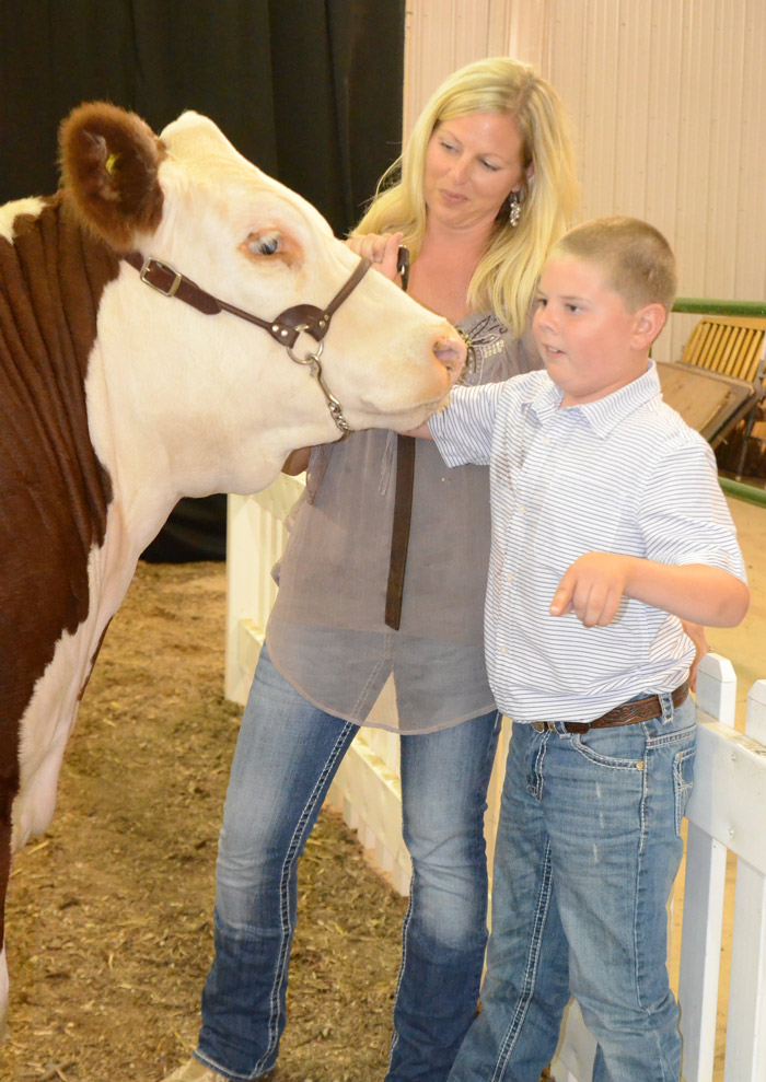 Janel Zehring gives her son Andon a little help in the auction ring.