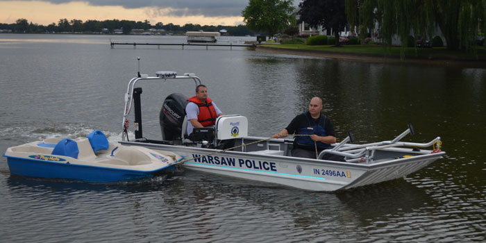 Officers tow the missing paddle boat back to shore. (Photos by Amanda McFarland)