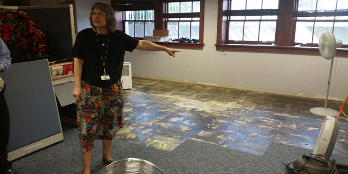 WCPL Director shows the board some of the floor damage done during June's heavy rains. (Photo by Amanda McFarland)