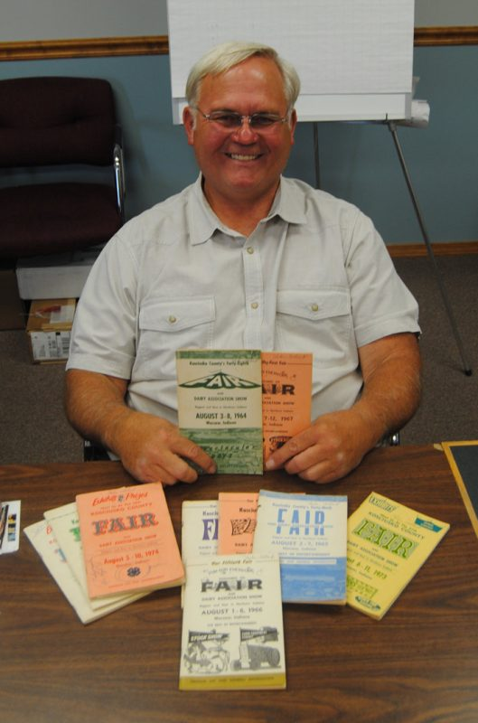The Kosciusko County Community Fair is celebrating its 100th anniversary. Pictured is Steve Trump, a former, seven-time fair board president, looking at older fair books. (Photo by Phoebe Muthart)