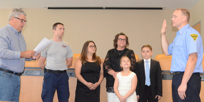 Warsaw Mayor Joe Thallemer, left, administers the oath of office to Firefighter Trent Stamper, right. Looking on are Quin Stamper, brother; Lili Stamper, wife; Peggy Stamper, mother; and children Laila and Wyatt. (Photos by Deb Patterson)
