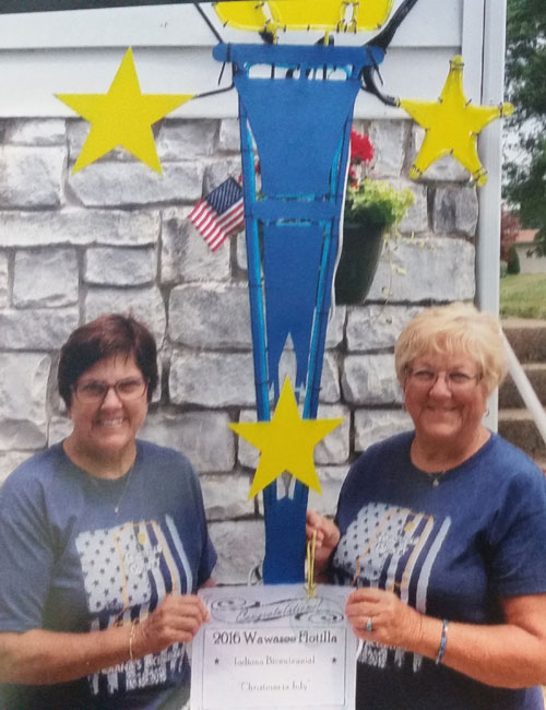 Cathy Baker, left, and Carolyn Lemberg pose in front of a torch after being named Bicentennial Torchbearers.