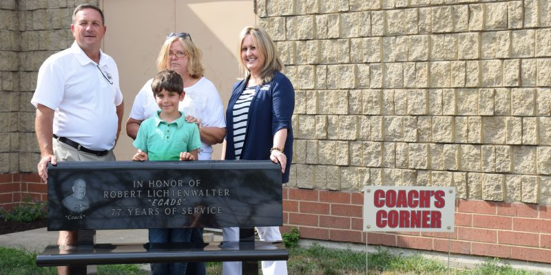 Tracy Furnivall, executive director, Judy Kinsey, Lichtenwalter's daughter, Tamara Drake, program director and Remi Iqbal, Lichtenwalter's great grandson all pose with the memorial being in Coach's Corner. (Photos by Maggie Kenworthy)