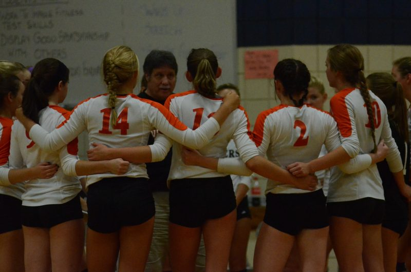 The Warsaw volleyball team listens to instructions from coach Rick Ashmore.