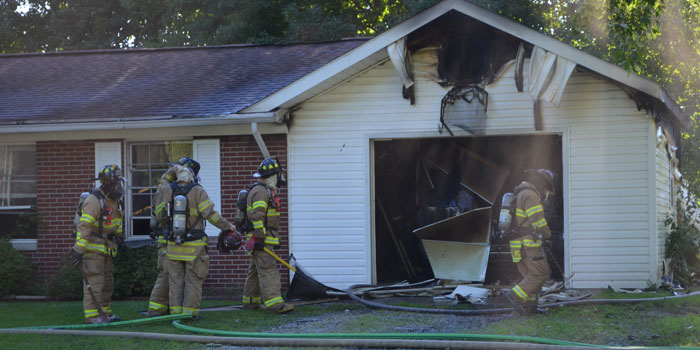Firefighters wait outside to make sure the fire is out. (Photos by Amanda McFarland)