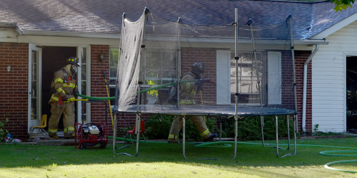 Firefighters exit the home, where there was smoke damage.
