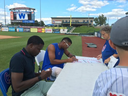 Jose Paulino, near, signs autographs for fans Sunday, Aug. 7. Paulino was named the July Pitcher of the Month, and sits with Cubs' May Player of the Month Eloy Jimenez.
