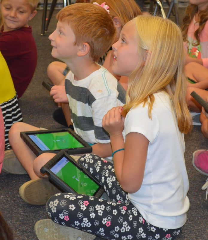 Jaxon Fawley, left, and Sophia Maule are anticipating seeing the results of a math exercise they had been doing on their iPads in Julie Hays' second-grade classroom at Syracuse Elementary.