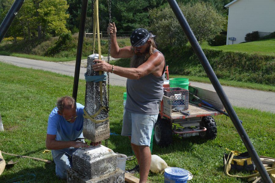"John ""Walt"" Walters, right, and his brother, Larry Walters, are working on stabilizing a grave marker at the Pleasant View Cemetery in Prairie Township."