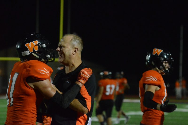 Warsaw football coach Phil Jensen congratulates Jack Tucker after his interception return for a touchdown Friday night. The Tigers routed Goshen 43-14.