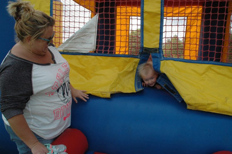 Tara Brandon, left, plays peek-a-boo with niece, Kambry Myers, at the North Webster Fall Festival bouncy castle