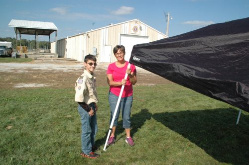 Mary Brower, right, helped her son Evan, left, a North Webster boy scout, take down their popcorn tent after the fall festival.