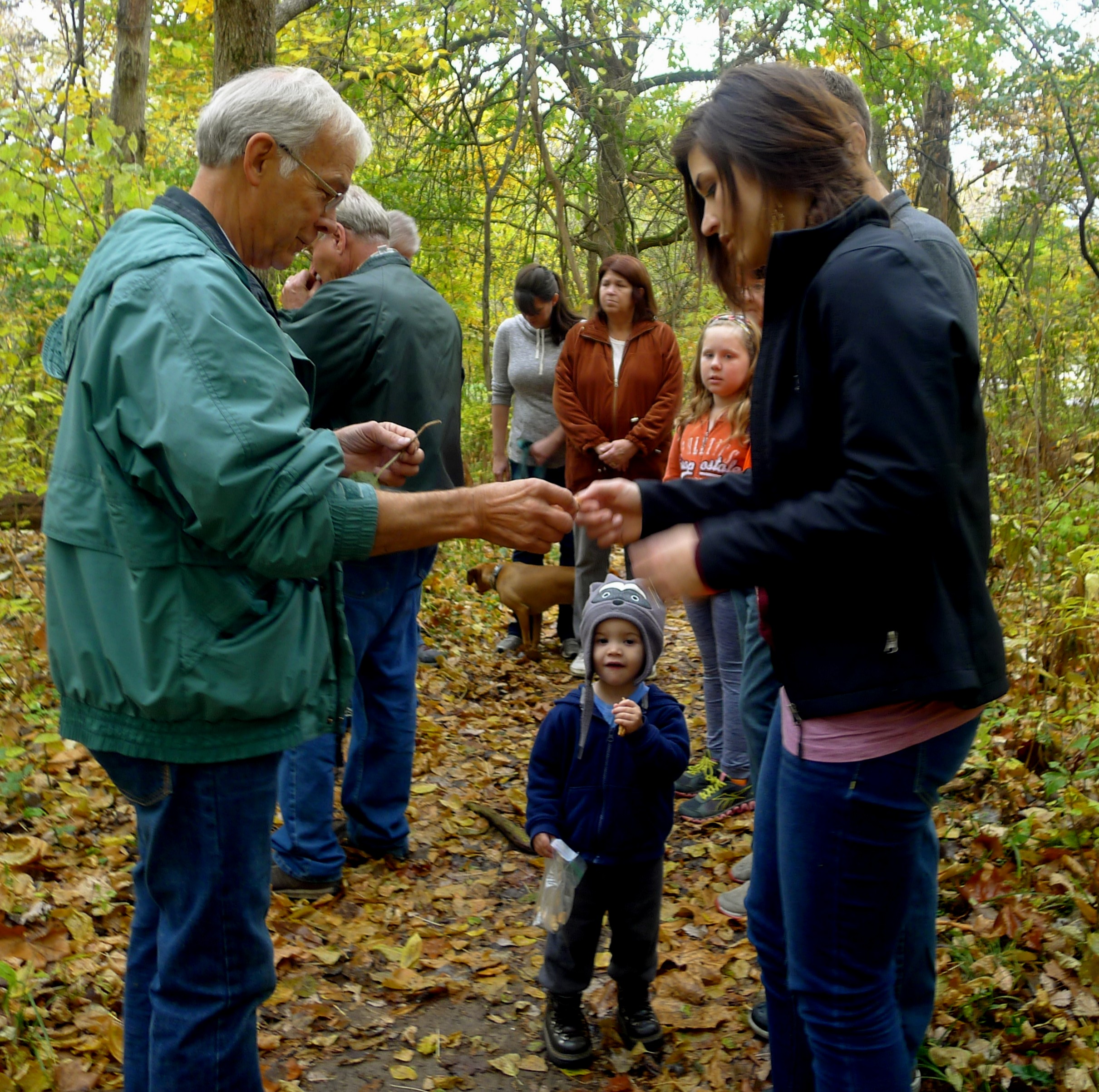 Luke Hunt, a certified naturalist in Indiana, leads the 2015 fall interpretive hike attendees through Heritage Trail in Winona Lake, noting natural features found along the trail.