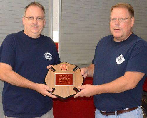 Rodney Bray, Milford Fire Department, receives the county fireman's Service Award, from Milford Fire Chief Todd Haines.