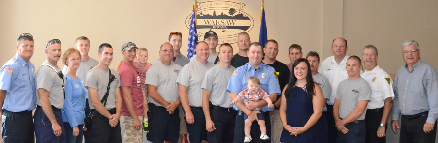 Members of the Warsaw-Wayne Fire Territory pose for a photo following the oath of office given to Miles Waters, shown in front holding his son Zanders, and next to his wife Elizabeth.