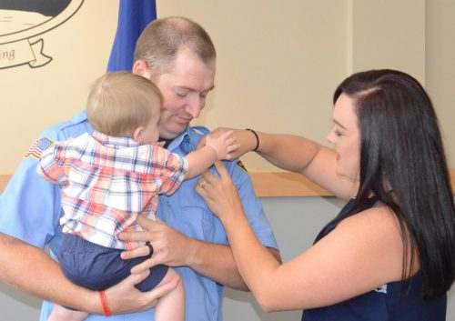 Zander Waters gives his mother, Elizabeth, a helping hand, pinning the firefighter badge on his father's shirt. Miles Waters was sworn in as a new full time officer of the department.