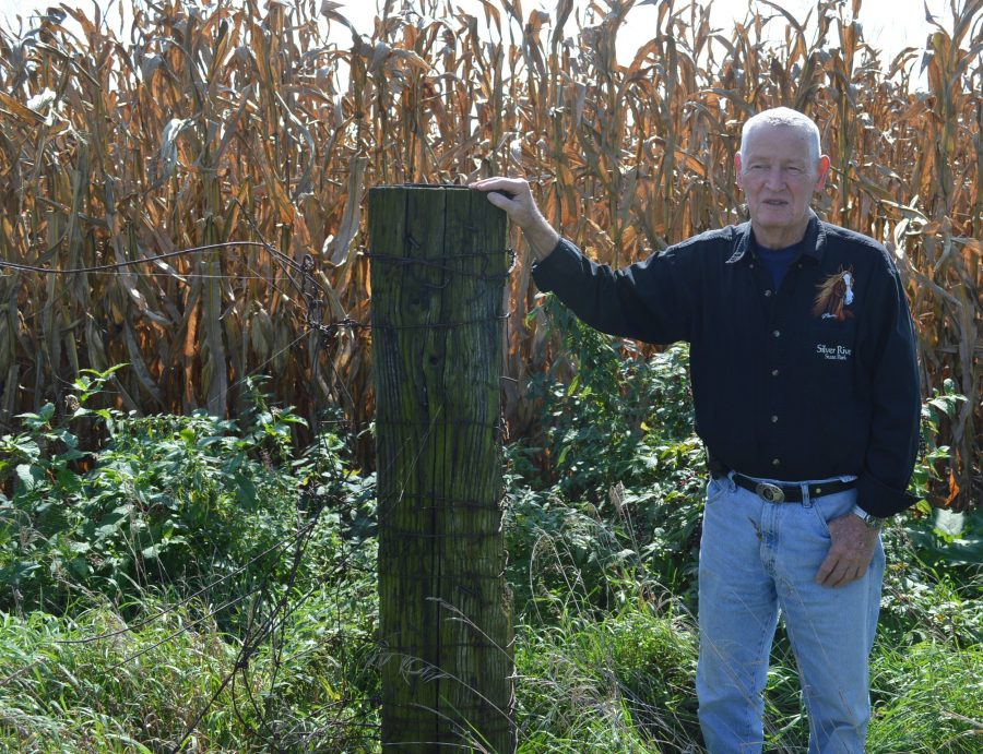 Eddie Creighton stands next to an old railroad tie used in a fence line many years ago on the former Myers farm in Harrison Township. Behind him is corn waiting to be harvested.